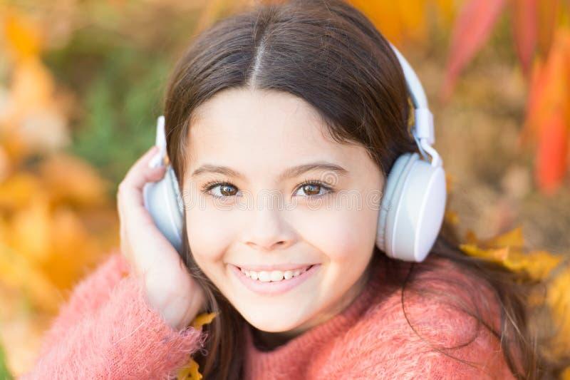Δώστε μέσα στο αυλάκι Ευτυχή ακουστικά ένδυσης παιδιών Λίγος οπαδός μουσικής την ημέρα φθινοπώρου Ευτυχές μικρό κορίτσι το φθινόπ στοκ εικόνες με δικαίωμα ελεύθερης χρήσης