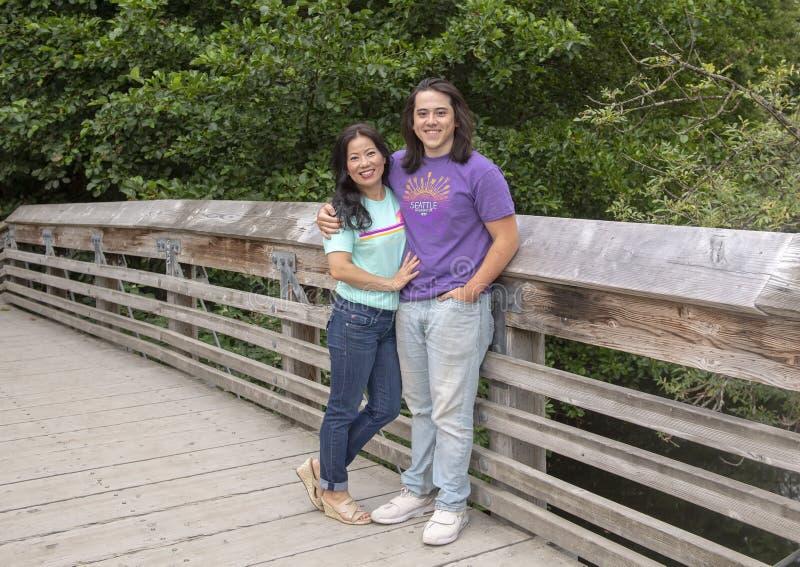 Είκοσι δύο χρονών Amerasian αρσενικό και η τοποθέτηση μητέρων του στην ξύλινη γέφυρα στο δενδρολογικό κήπο πάρκων της Ουάσιγκτον, στοκ φωτογραφία με δικαίωμα ελεύθερης χρήσης