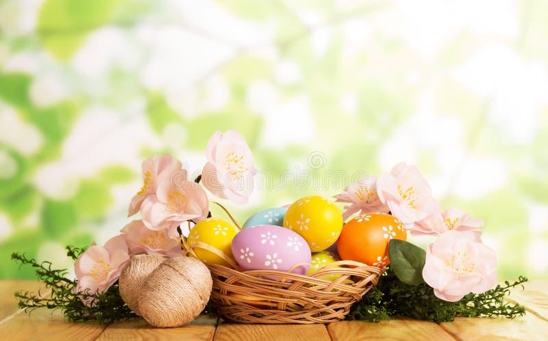 Είναι διαφορετικά αυγά Πάσχας στο καλάθι και πλησιάζει, χλόη, λουλούδια στοκ φωτογραφία με δικαίωμα ελεύθερης χρήσης