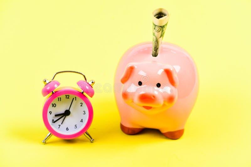 Είναι χρόνος να πάρει πλούσιο αποχώρηση o ίδρυση επιχείρησης οικονομική θέση piggy τράπεζα με το ξυπνητήρι στοκ εικόνες