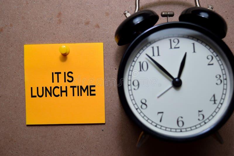 Είναι ώρα για φαγητό, γράψτε στην σημείωση σε ξύλινο τραπέζι στοκ εικόνες