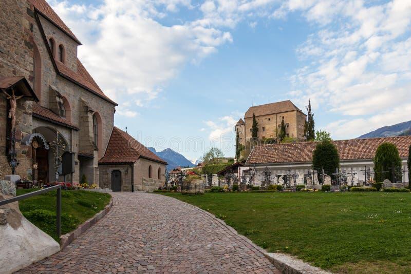 Είσοδος στην παλαιά εκκλησία, Alte Kirche, με το τετράγωνο και το Castle Schenna νεκροταφείων στο υπόβαθρο Scena, νότιο Τύρολο, Ι στοκ εικόνα