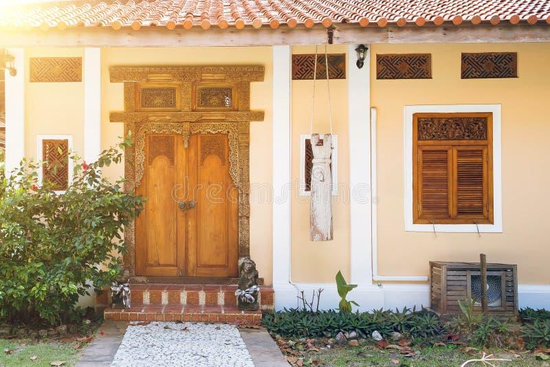 Είσοδος στο κίτρινο σπίτι με τα ξύλινα χαρασμένα παραθυρόφυλλα Παλαιά ξύλινη πόρτα με τα χαρασμένα σχέδια Πέτρινη πορεία που οδηγ στοκ εικόνα