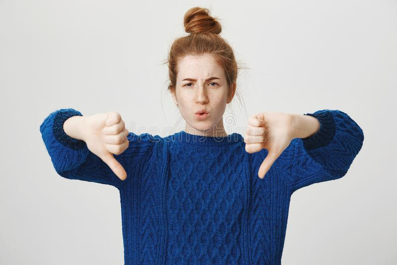 Είστε ηττημένος Το πορτρέτο το ελκυστικό redhead κορίτσι στο περιστασιακό χειμερινό πουλόβερ που παρουσιάζει αντίχειρες κάτω στοκ φωτογραφίες
