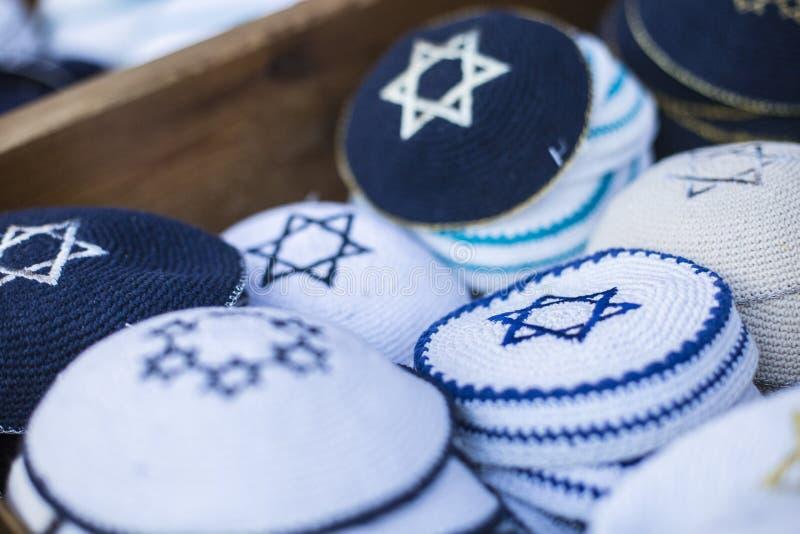 Εβραϊκά θρησκευτικά καλύμματα (yarmulke) στο πεζοδρόμιο πετρών κοντά στο κατάστημα αναμνηστικών στο εβραϊκό τέταρτο της παλαιάς π στοκ φωτογραφία με δικαίωμα ελεύθερης χρήσης