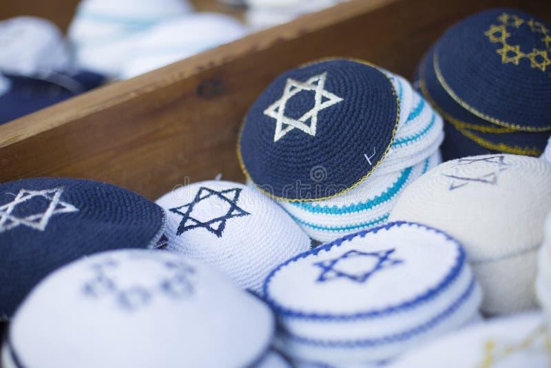 Εβραϊκά θρησκευτικά καλύμματα (yarmulke) στο πεζοδρόμιο πετρών κοντά στο κατάστημα αναμνηστικών στο εβραϊκό τέταρτο της παλαιάς π στοκ εικόνες