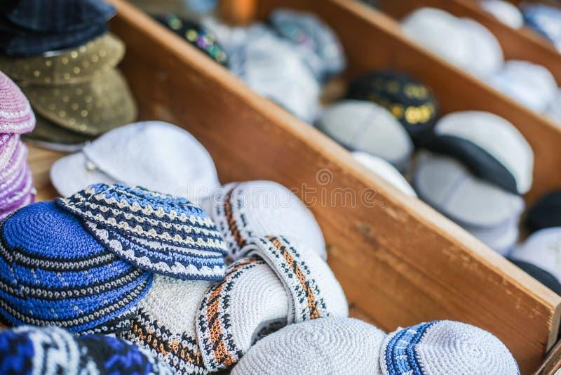Εβραϊκά θρησκευτικά καλύμματα (yarmulke) στο πεζοδρόμιο πετρών κοντά στο κατάστημα αναμνηστικών στο εβραϊκό τέταρτο της παλαιάς π στοκ εικόνα με δικαίωμα ελεύθερης χρήσης