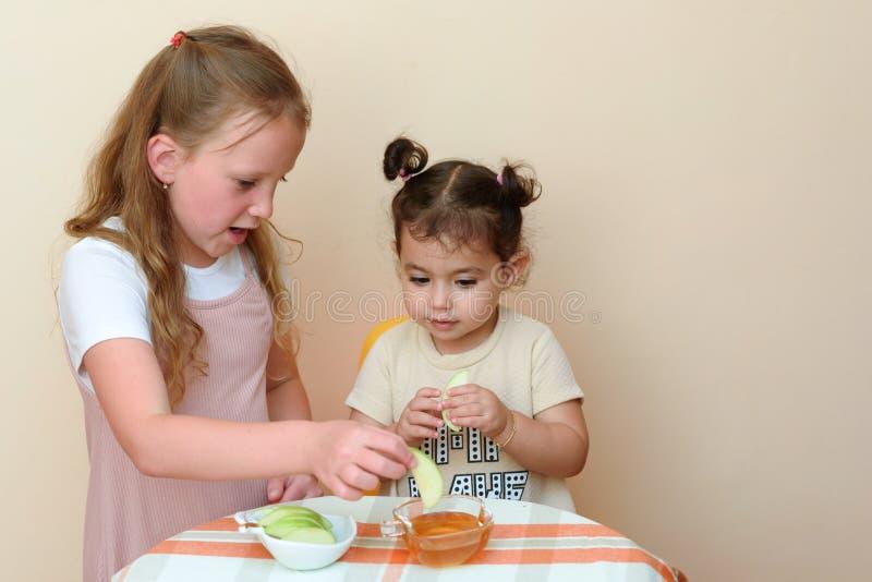 Εβραϊκά παιδιά που βυθίζουν τις φέτες μήλων στο μέλι σε Rosh HaShanah στοκ φωτογραφία