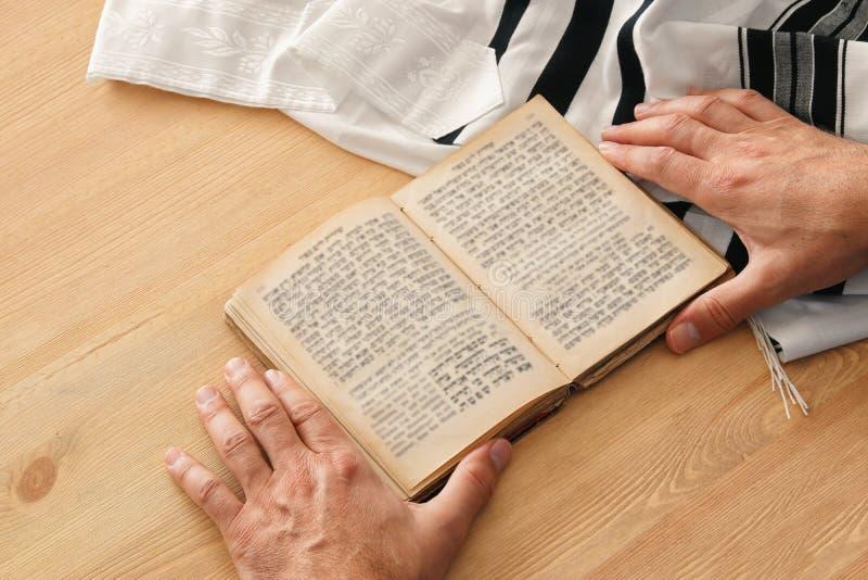 Εβραϊκά χέρια ατόμων που κρατούν ένα βιβλίο προσευχής, που προσεύχεται, δίπλα στο tallit Εβραϊκά παραδοσιακά σύμβολα Holida έτους στοκ εικόνες με δικαίωμα ελεύθερης χρήσης