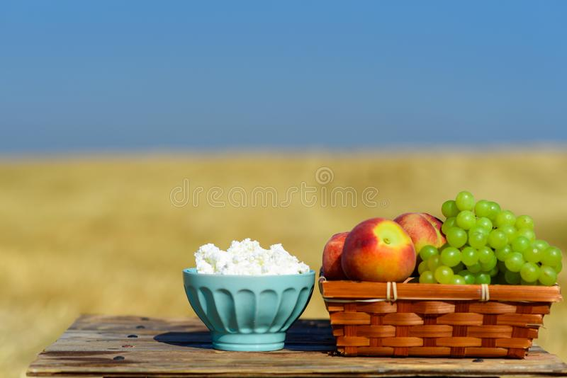 Εβραϊκές διακοπές Shavuot, φεστιβάλ συγκομιδών Τυρί εξοχικών σπιτιών, και καλάθι φρούτων στον ξύλινο πίνακα πέρα από το υπόβαθρο  στοκ φωτογραφίες