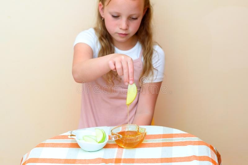 Εβραϊκές φέτες μήλων παιδιών βυθίζοντας στο μέλι σε Rosh HaShanah στοκ εικόνες με δικαίωμα ελεύθερης χρήσης