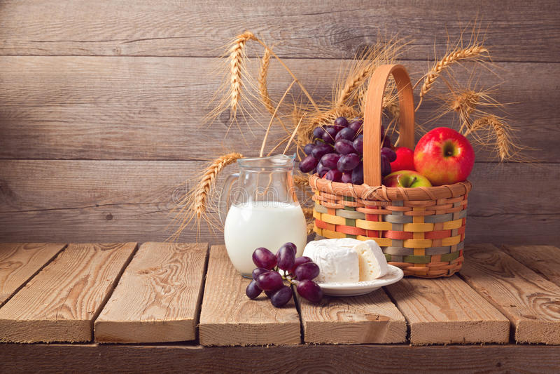 Εβραϊκός εορτασμός Shavuot διακοπών Καλάθι με τα φρούτα και γάλα πέρα από το ξύλινο υπόβαθρο στοκ φωτογραφία