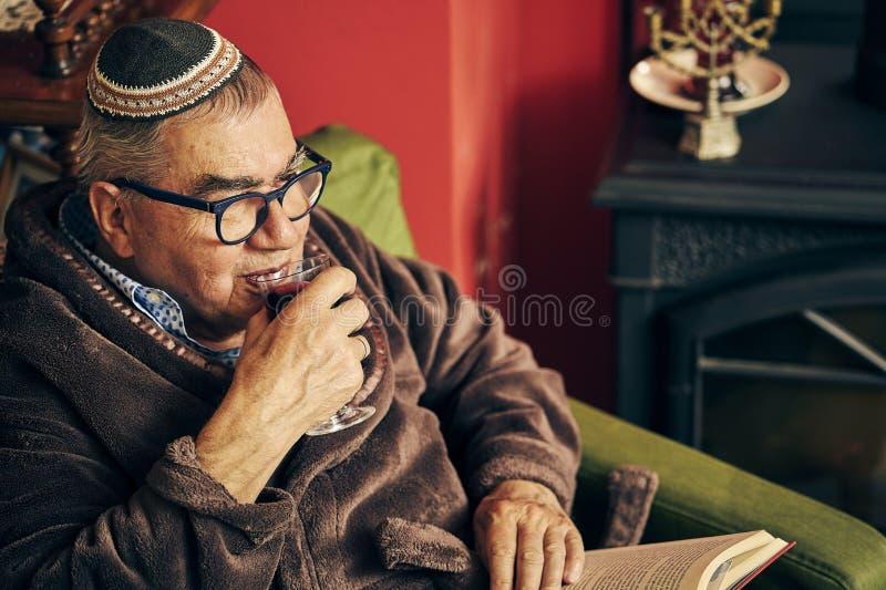 Εβραϊκός πρεσβύτερος που διαβάζει ένα βιβλίο torah και που πίνει το kosher κρασί στοκ φωτογραφία