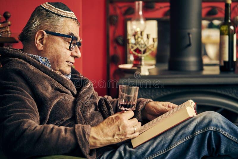 Εβραϊκός πρεσβύτερος που διαβάζει ένα βιβλίο torah και που πίνει το kosher κρασί στοκ εικόνα