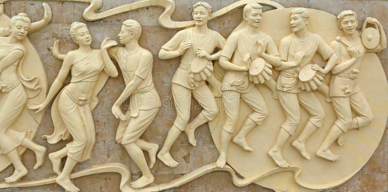 Εγγενής χάραξη πετρών χορού ανθρώπων πολιτισμού ταϊλανδική στον τοίχο ναών στοκ εικόνα