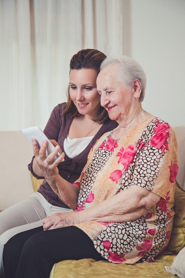 Εγγονή και γιαγιά που εξετάζουν το κινητό τηλέφωνο στοκ εικόνα