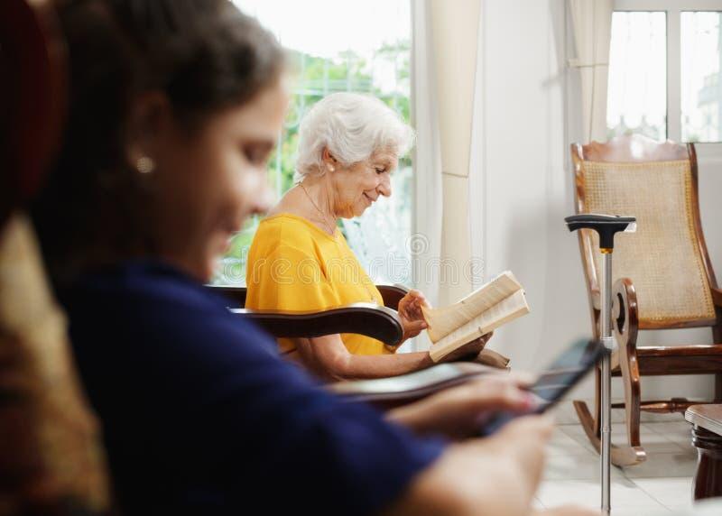 Εγγονή που χρησιμοποιεί το κινητά τηλέφωνο και το βιβλίο ανάγνωσης Grandma στοκ εικόνες