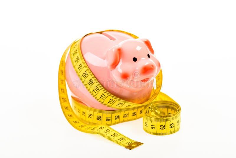 Εγγυοδοσία χαμηλός πληρώστε Χρήματα αποταμίευσης Κατάθεση piggy τράπεζα με την ταινία μέτρησης moneybox διατροφή χρημάτων χρηματο στοκ φωτογραφίες