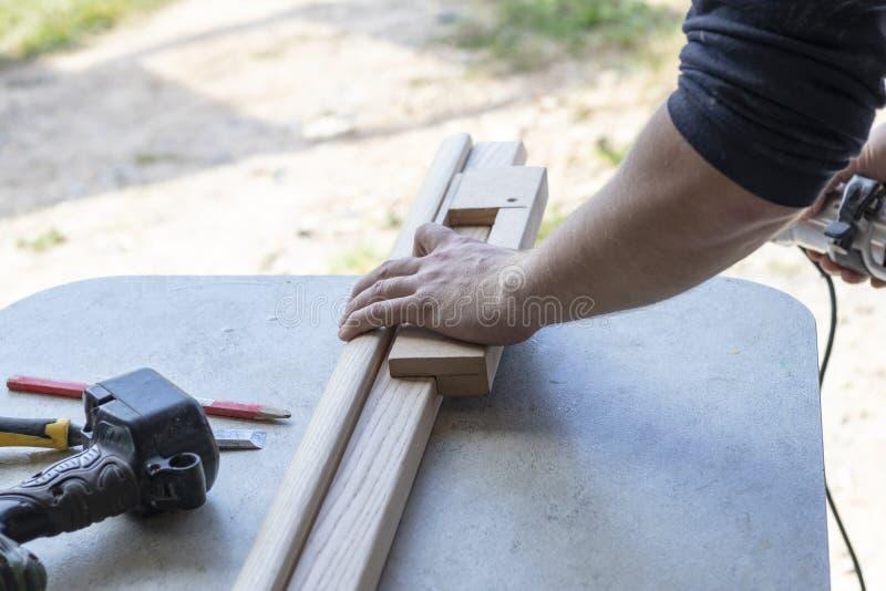 Εγκαθιστώντας μια πόρτα, Εγκαταστήστε μια κλειδαριά, χρησιμοποιήστε ένα πριόνι φρεζαρίσματος, ένας ξυλουργός που κλείνει κρατά έν στοκ φωτογραφία