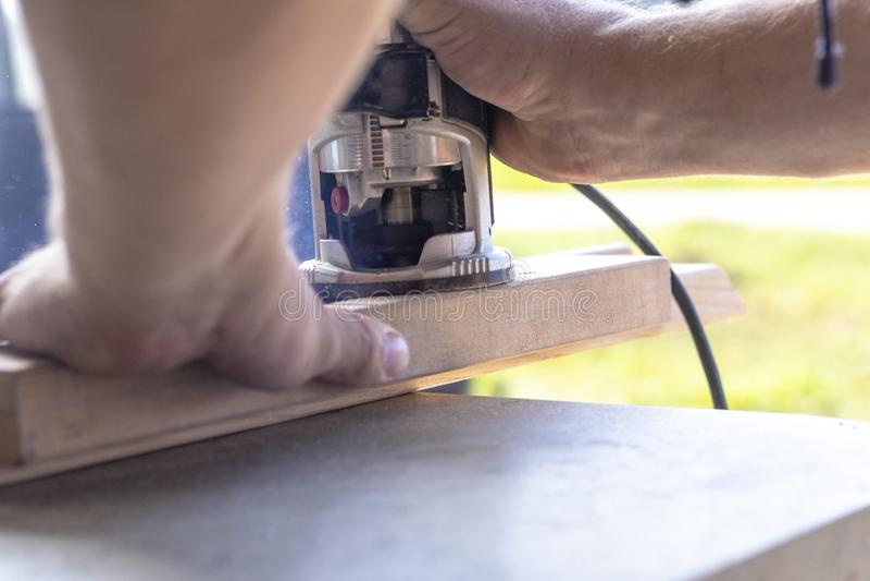 Εγκαθιστώντας μια πόρτα, Εγκαταστήστε μια κλειδαριά, χρησιμοποιήστε ένα πριόνι φρεζαρίσματος, ένας ξυλουργός που κλείνει κρατά έν στοκ εικόνες