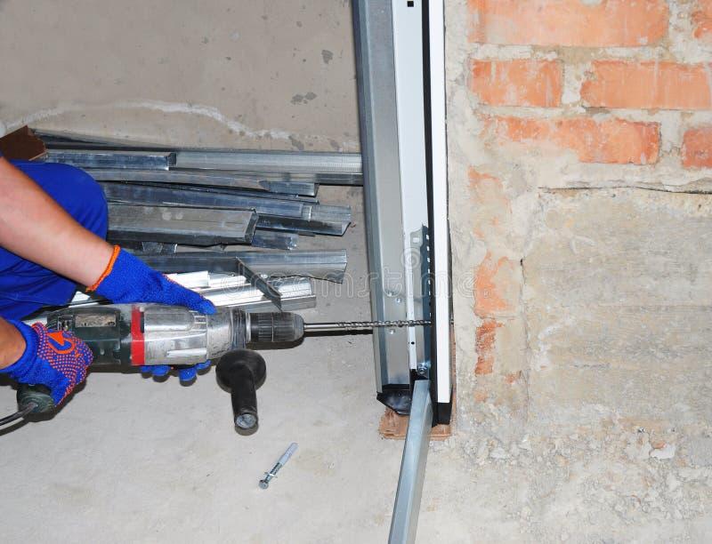 Εγκατάσταση & αντικατάσταση πορτών γκαράζ Εγκαταστήστε το ανοιχτήρι πορτών γκαράζ & πορτών γκαράζ Πώς να εγκαταστήσει μια πόρτα γ στοκ εικόνες