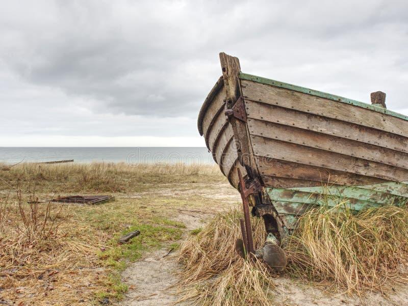 Εγκαταλειμμένη βάρκα που κολλιέται στην άμμο Παλαιά ξύλινη βάρκα στην αμμώδη ακτή στοκ φωτογραφία