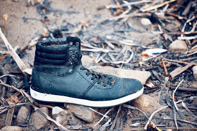 Εγκαταλειμμένη ενιαία υγρή μαύρη μπότα που στέκεται στη λάσπη στοκ φωτογραφίες