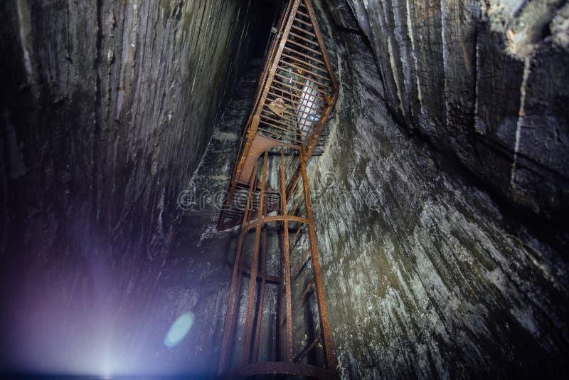 Εγκαταλειμμένος βαθιά κάθετος άξονας υπόγειων ορυχείων Παλαιά σκουριασμένη σκάλα σιδήρου στοκ εικόνες με δικαίωμα ελεύθερης χρήσης