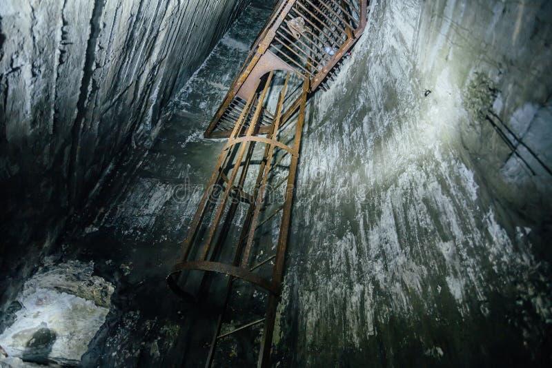 Εγκαταλειμμένος βαθιά κάθετος άξονας υπόγειων ορυχείων Παλαιά σκουριασμένη σκάλα σιδήρου στοκ φωτογραφία με δικαίωμα ελεύθερης χρήσης