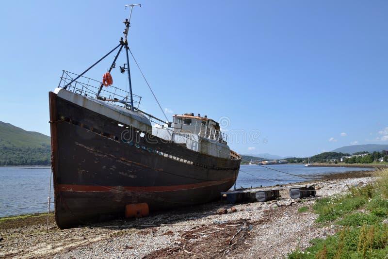 Εγκαταλειμμένο εκλεκτής ποιότητας αλιευτικό σκάφος παραλία κοντά στο χωριό Corpach, οχυρό William, Σκωτία, Ηνωμένο Βασίλειο στοκ φωτογραφία