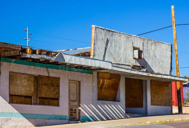 Εγκαταλειμμένο εμπορικό κτήριο με επιβιβασμένος επάνω στα παράθυρα στοκ εικόνα με δικαίωμα ελεύθερης χρήσης