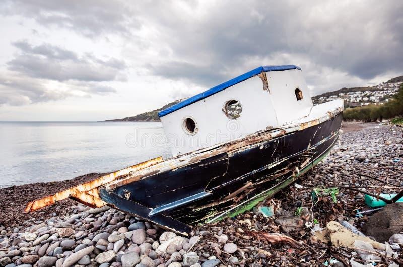 Εγκαταλειμμένο παλαιό αλιευτικό σκάφος στην ακτή μια ευμετάβλητη χειμερινή ημέρα στοκ φωτογραφία με δικαίωμα ελεύθερης χρήσης