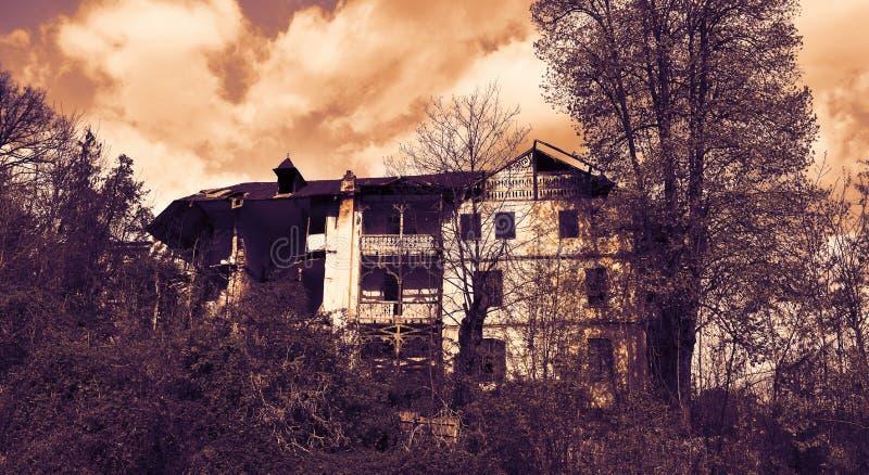 Εγκαταλειμμένο παλαιό συχνασμένο σπίτι με τη σκοτεινή ατμόσφαιρα φρίκης στο σεληνόφωτο στοκ εικόνες με δικαίωμα ελεύθερης χρήσης