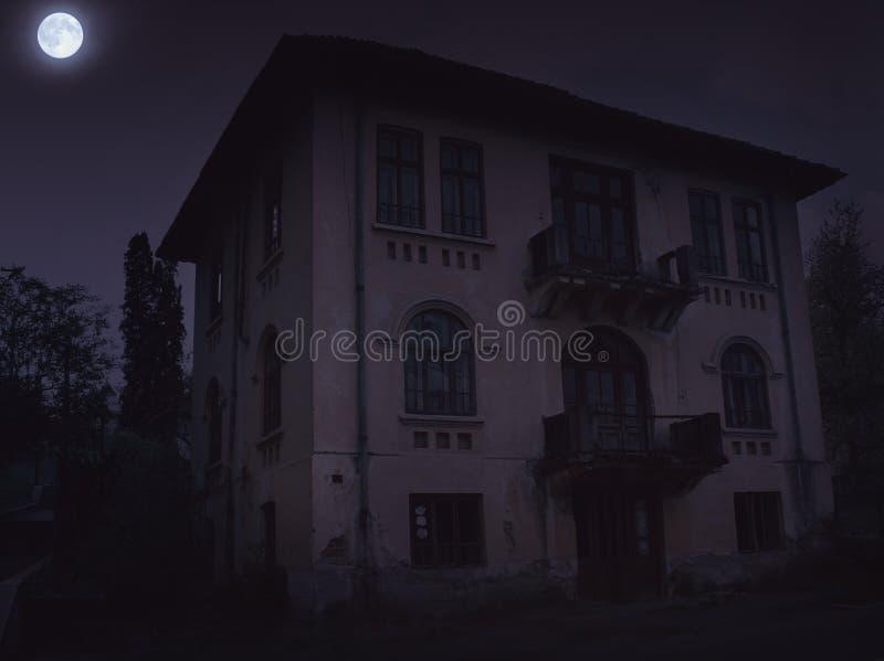 Εγκαταλειμμένο παλαιό συχνασμένο σπίτι με τη σκοτεινή ατμόσφαιρα φρίκης στο σεληνόφωτο στοκ φωτογραφίες