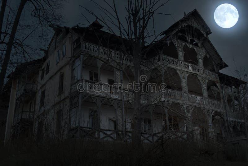 Εγκαταλειμμένο παλαιό συχνασμένο σπίτι με τη σκοτεινή ατμόσφαιρα φρίκης στο σεληνόφωτο στοκ φωτογραφία με δικαίωμα ελεύθερης χρήσης