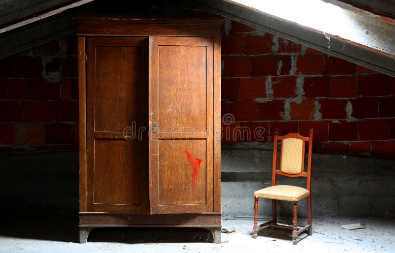 εγκαταλειμμένο σπίτι με το ξύλινο ντουλάπι και μια καρέκλα στοκ εικόνες