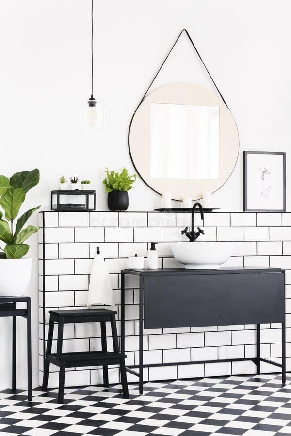 Εγκαταστάσεις και καθρέφτης στο γραπτό εσωτερικό λουτρών με το ελεγμένα πάτωμα και το σκαμνί Πραγματική φωτογραφία στοκ εικόνες με δικαίωμα ελεύθερης χρήσης