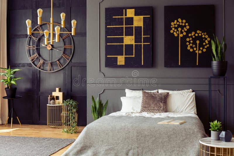 Εγκαταστάσεις και μαύρες και χρυσές αφίσες στο γκρίζο εσωτερικό κρεβατοκάμαρων με το ρολόι και το κρεβάτι με τα μαξιλάρια Πραγματ στοκ φωτογραφίες με δικαίωμα ελεύθερης χρήσης