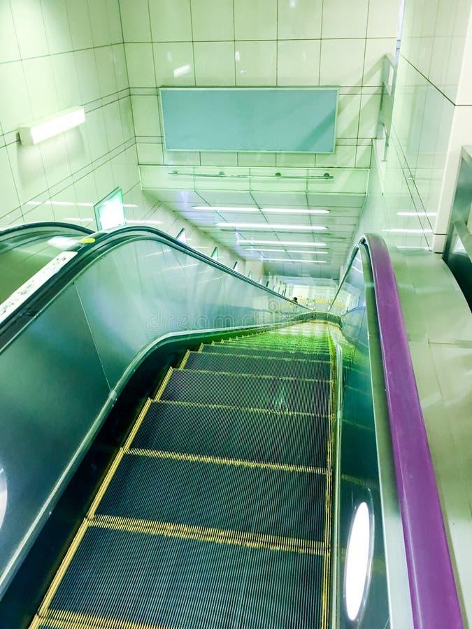 εγκαταστάσεις κυλιόμενων σκαλών που οδηγούν κάτω σε έναν σταθμό μετρό με τα φω'τα νέου, κινούμενη σκάλα στοκ φωτογραφία με δικαίωμα ελεύθερης χρήσης
