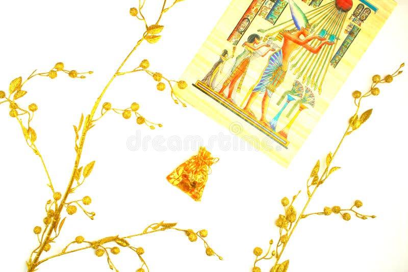 Εγκαταστάσεις του χρυσού χρώματος, ενός σχεδίου στον πάπυρο και των διακοσμήσεων σε μια σακούλα στοκ φωτογραφία με δικαίωμα ελεύθερης χρήσης