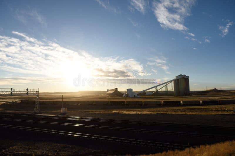 Εγκαταστάσεις φόρτωσης βιομηχανικού σιλό άνθρακα και αμαξοστοιχιών κατά το ηλιοβασίλεμα στοκ φωτογραφία με δικαίωμα ελεύθερης χρήσης