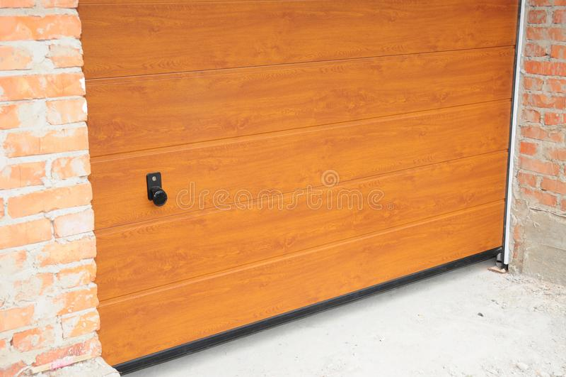 Εγκαταστήστε την πόρτα γκαράζ καινούργιων σπιτιών Εγκατάσταση πορτών γκαράζ, μόνωση Η κατοικημένη πόρτα γκαράζ εγκαθιστά στοκ φωτογραφίες με δικαίωμα ελεύθερης χρήσης