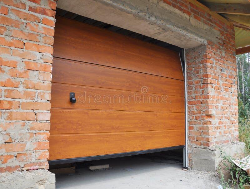 Εγκαταστήστε την πόρτα γκαράζ καινούργιων σπιτιών Εγκατάσταση πορτών γκαράζ στοκ φωτογραφία με δικαίωμα ελεύθερης χρήσης