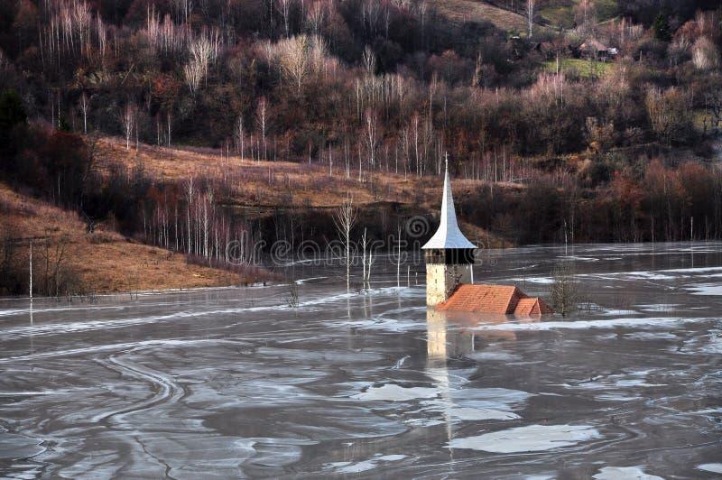 Εγκαταλειμμένη εκκλησία σε μια λίμνη λάσπης. Φυσική καταστροφή μεταλλείας με το wat στοκ φωτογραφία