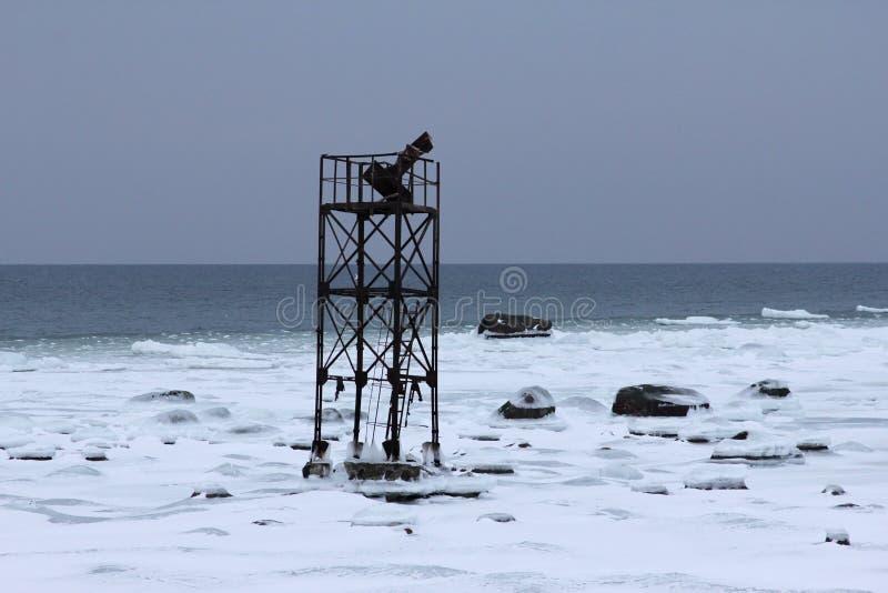 Εγκαταλειμμένος θαλάσσιος πύργος σε ένα χιόνι στην ακτή στοκ φωτογραφία