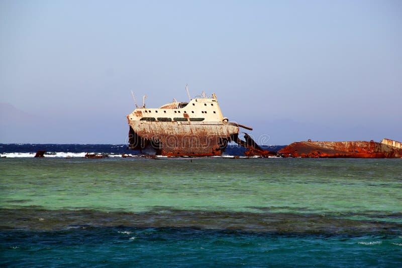 Εγκαταλειμμένο σκουριασμένο σκάφος στα μπλε κύματα θάλασσας στοκ εικόνα