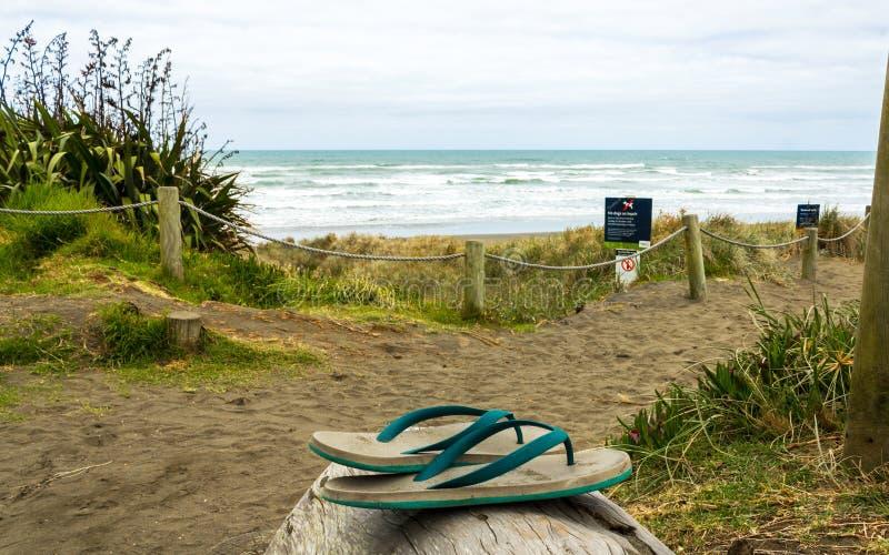 Εγκαταλειμμένο Jandals στην παραλία Aucland Νέα Ζηλανδία Muriwai στοκ εικόνες