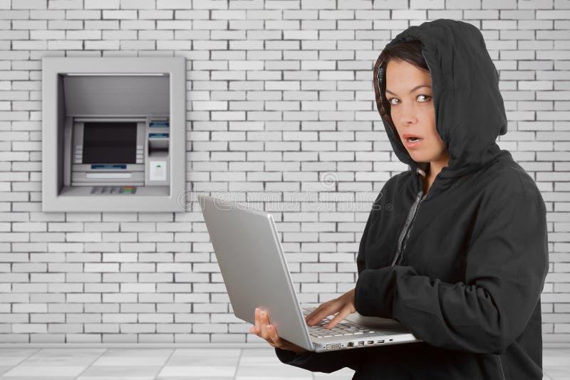 Εγκληματικός χάκερ γυναικών που φορά την κουκούλα στη χρησιμοποίηση ενός lap-top μπροστά από στοκ εικόνα