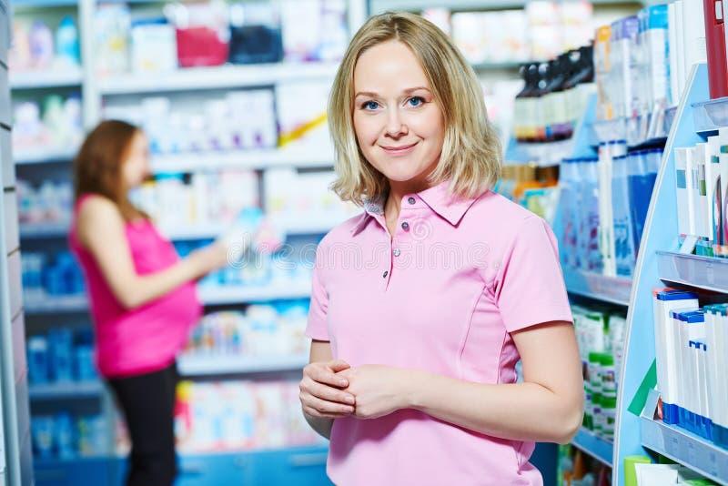Εγκυμοσύνη και φαρμακευτικά προϊόντα pharmaceutist με έγκυο στο υπόβαθρο στο κατάστημα στοκ εικόνα με δικαίωμα ελεύθερης χρήσης