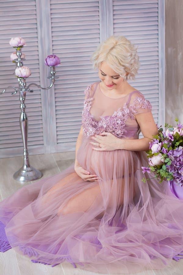 Εγκυμοσύνη, μητρότητα και ευτυχής μελλοντική έννοια μητέρων - η έγκυος γυναίκα στο αερώδες ιώδες φόρεμα με την ανθοδέσμη ανθίζει  στοκ εικόνες